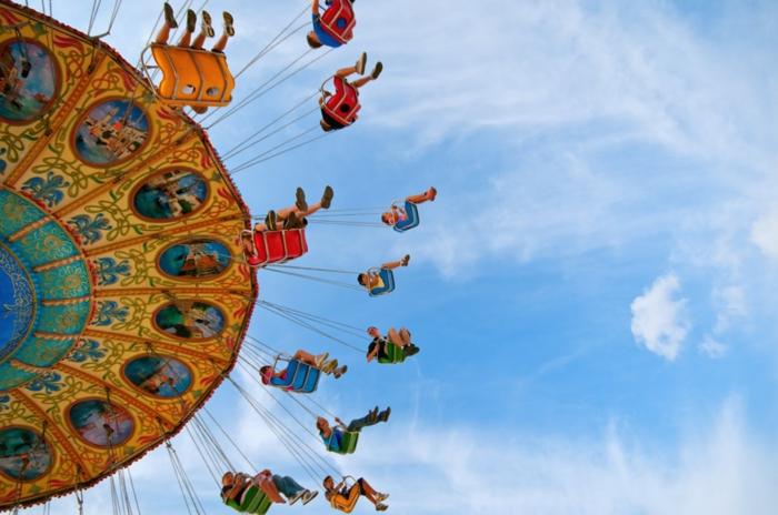 enfants les pieds en air, paysage paradisiaque, farniente sur le fond du ciel bleu clair, des sièges de carrousel en couleurs vives