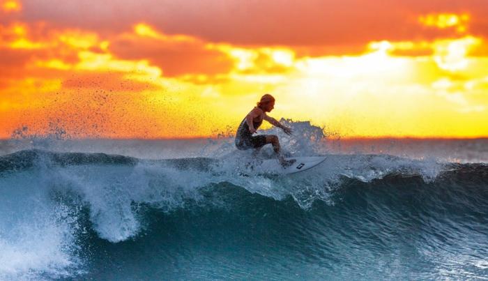 fond ecran paysage, beau paysage, ciel aux nuances oranges et rouges, surfeuse sur la vague avec son surf, eaux vertes transparentes