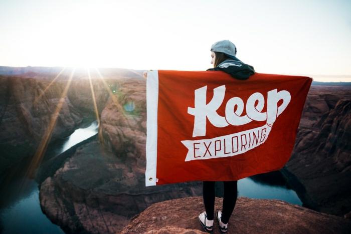 une fille avec casquette bleue au sommet d'une roche rouge, avec une enseigne en rouge et blanc Continue a explorer