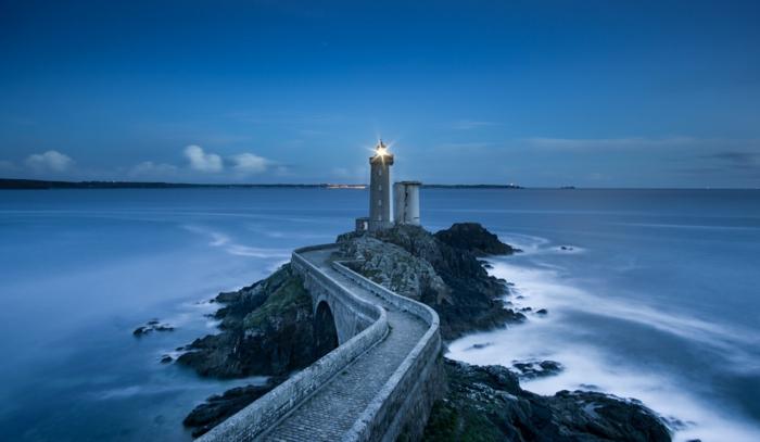 un phare maritime dans la nuit au bout d'un chemin en zig-zague, ciel bleu, rochers noirs, destination paradisiaque