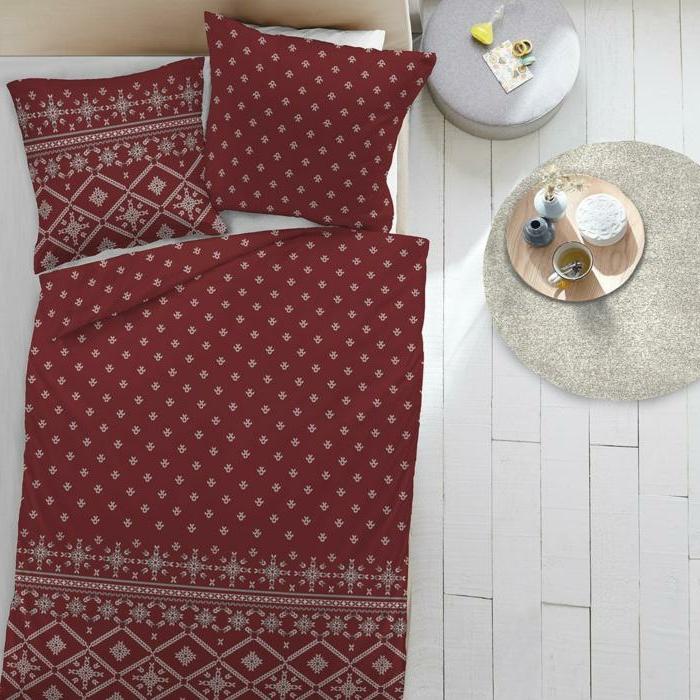 linge de lit couleur bordeaux, tabouret gris, sol en bois blanc, boire son thée