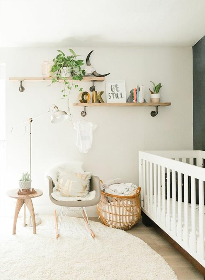 étagères jouets en bois clair, lit en blanc, tapis rond en couleur crème, mur en bleu canard, table en bois avec plan rond, fauteuil en tissu gris