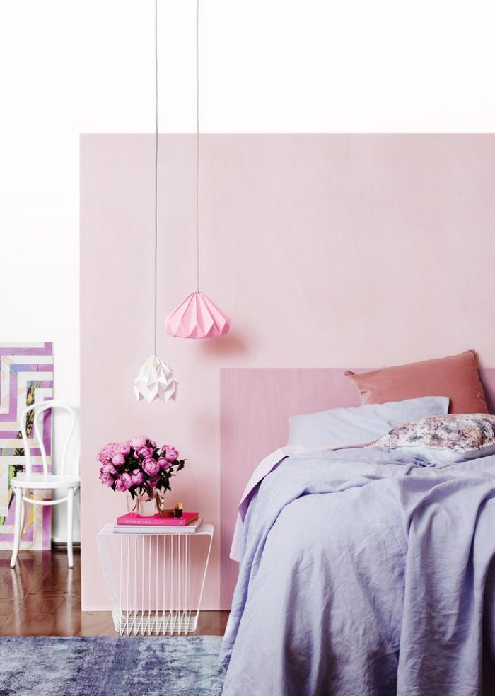 peinture murale de nuances rose et blanches, grand lit dans une chambre femme avec table basse et luminaires origami