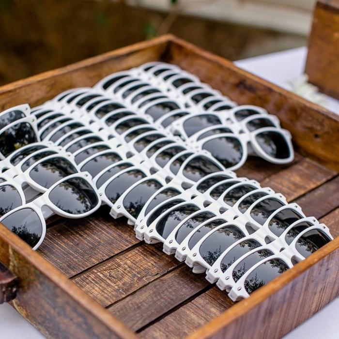 idée cadeau mariage pas cher, lunettes de soleil en blanc et noir à offrir aux invités d'un mariage sur la plage