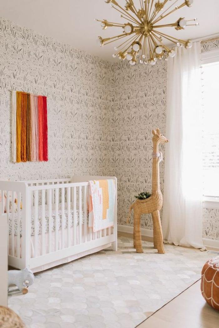 tapis chambre fille en gris et blanc, luminaire en forme de rayons en métal jaune, décoration murale en mailles de couleurs vives, murs recouverts de papier peint en gris et blanc, pouf marocain en cuir nuance tabac