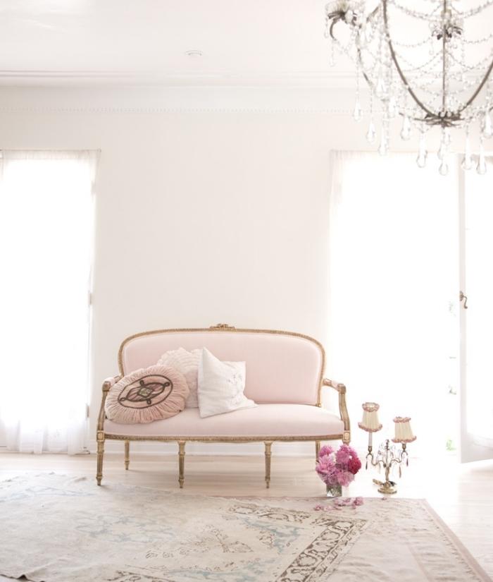 idée déco rétro chic dans un salon aux murs blancs avec parquet clair aménagé avec canapé en rose pastel et or