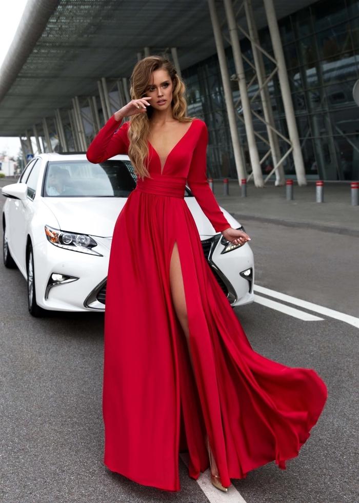 modèle de jolie robe rouge longue à design asymetrique avec décolleté en V et manches longues combinée avec sandales dorés
