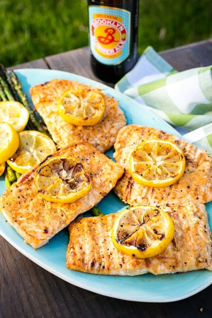 repas du soir léger, recette de tranches de saumon grillé avec garniture de citron et aubergines rôti servis dans une assiette bleue