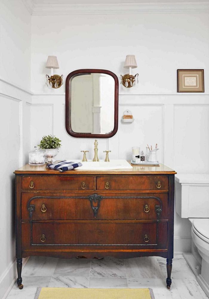 une commode salle de bain en bois antique avec ferrure en bronze transforméen meuble-vasque original pour une ambiance chic à l'ancienne