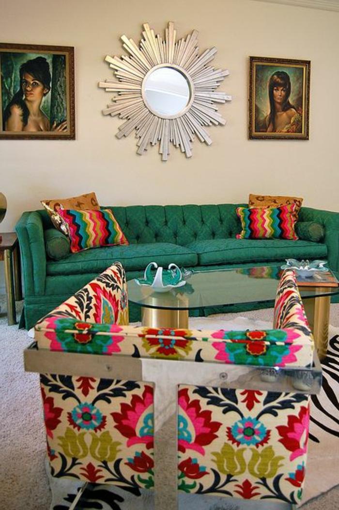 fauteuil bariolé, canapé vert, peinture urale beige, miroir décoratif, portraits de femme