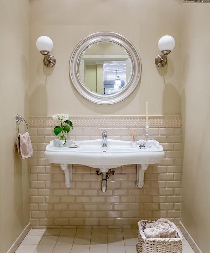 lavabo blanc vintage dans une salle de bain petite surface beige, miroir rond, panier rangement et lampes murales