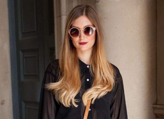 femme stylée habillée en chemise noire avec boutons blancs combinée avec accessoires sac à main camel et lunettes de soleil rondes, cheveux ombrés de base blond foncé