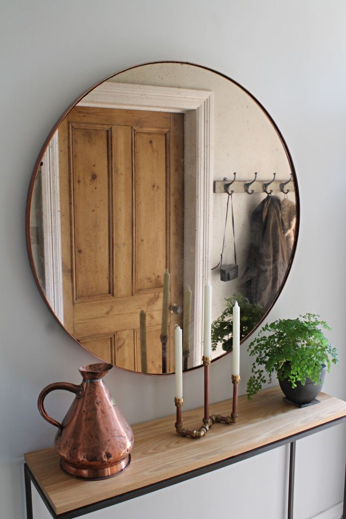 meuble couloir blanc et bois avec finitions noir matte, modèle de miroir rond et objets décoratifs de cuivre et or
