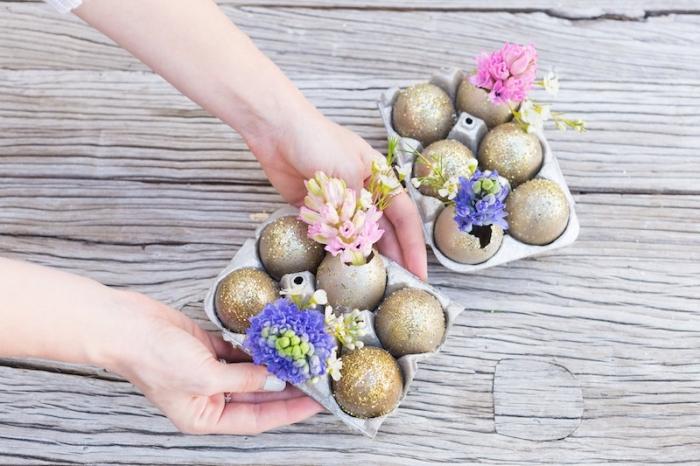idée de deco table paques avec oeufs vidés et peints en glitter doré en forme de vases avec fleurs, carton d'oeufs avec fleurs et coquilles décorées