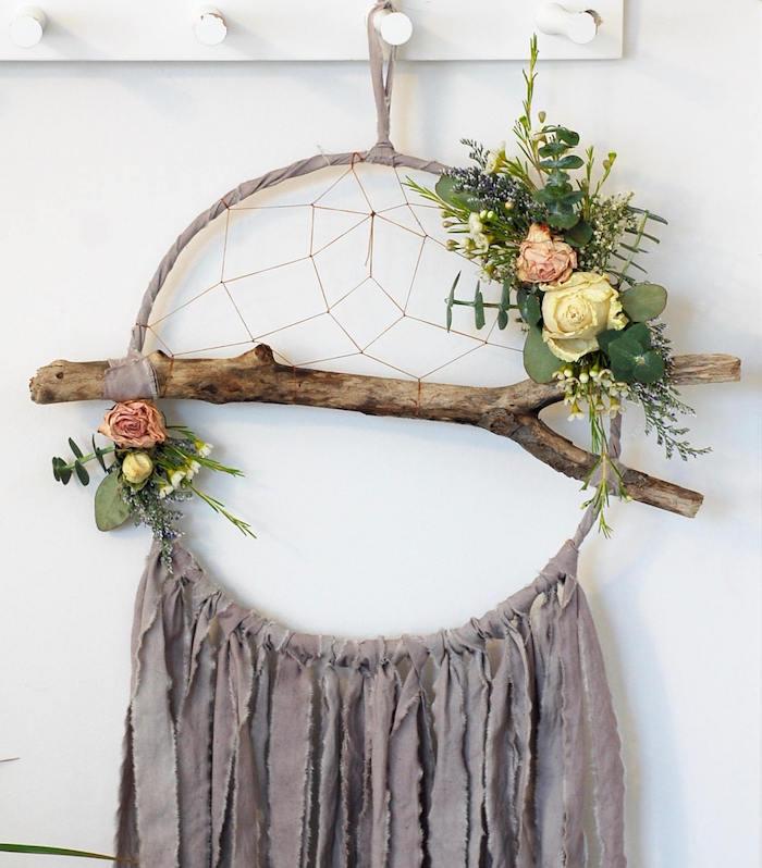 décoration maison en attrape reve fait main, cerceau enveloppé de bandes de tissu, frange de chutes de tissu grises, branche de bois, filet, deco florale