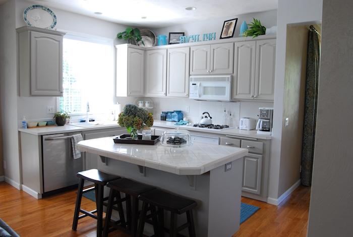 petite cuisine d'angle gris et blanc cassé avec petit ilot central clair