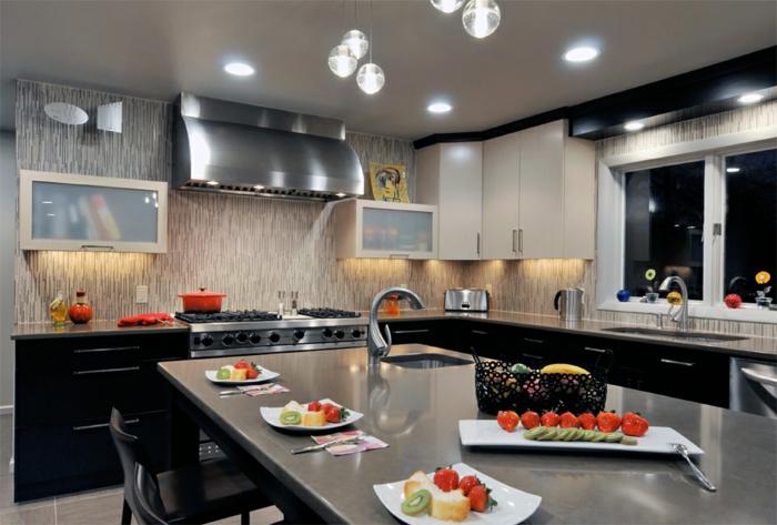 cuisine gris et blanc, hotte murale placards noirs et électroménager, grand îlot avec des chaises autour