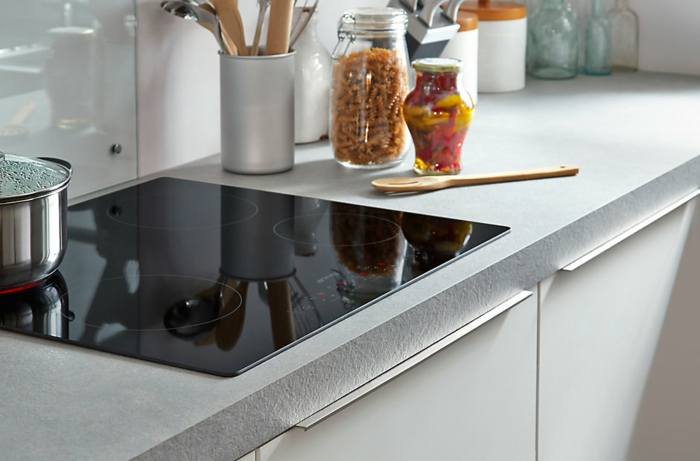 fourneax noirs dans une cuisine laquée blanche, plan de travail gris et base blanche, angle de cuisine bien organisé