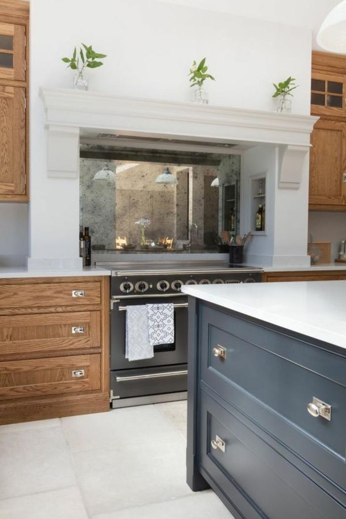 cuisine blanc laqué, meubles en beige et en bleu canard, grande cheminée et fourneaux noirs, dalles de carrelage blanches, style de cuisine classique avec des meubles massifs