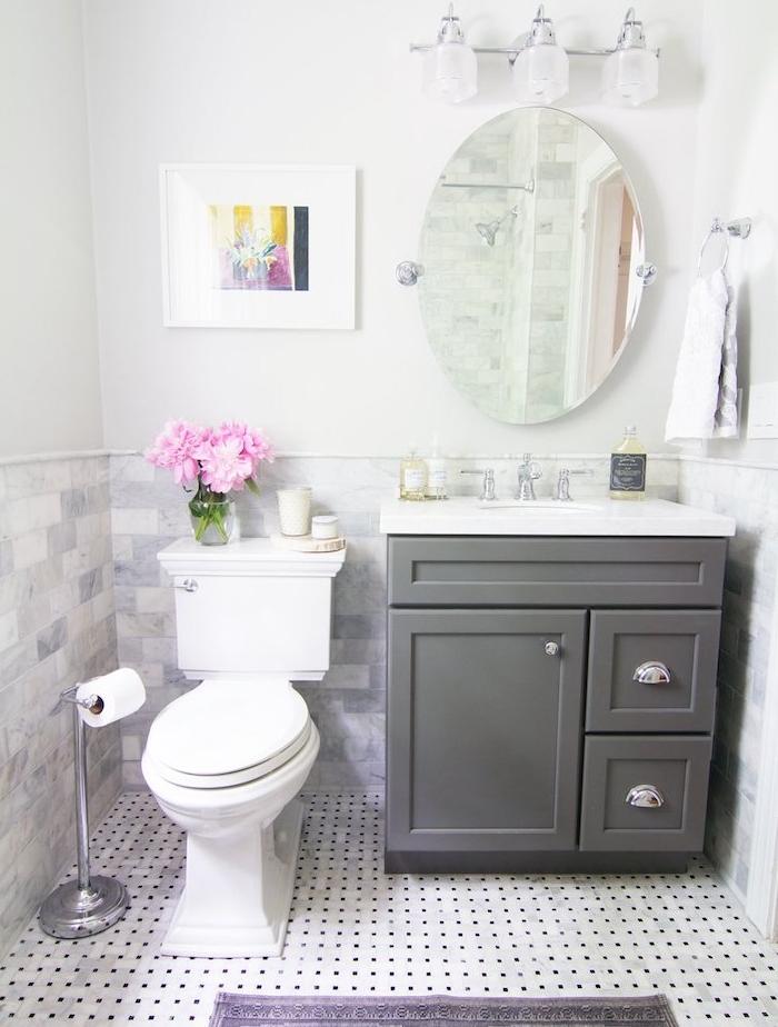petite salle de bain design avec wc blanc, meuble sous vasque gris, carrelage sol blanc à pois noirs, miroir oval, éclairage sdb