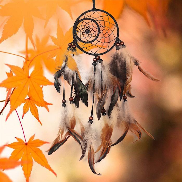 fabriquer un attrape reve avec des cerceaux noirs intégrés, toile noire, plumes marron et noirs, fond feuilles d automne