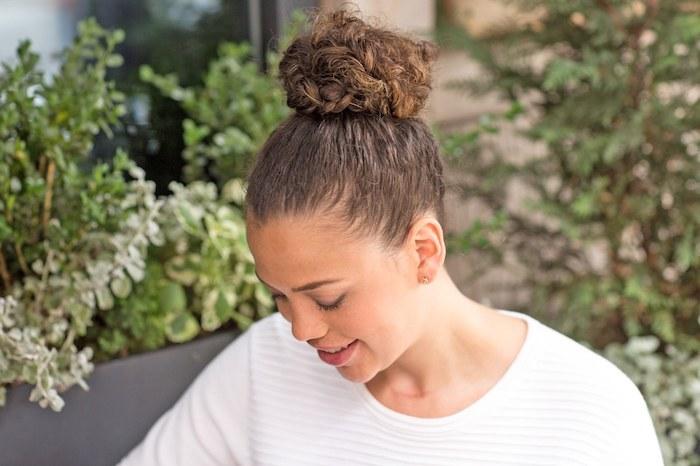 exemple de chignon haut tressé, femme métisse coiffure cheveux frisés élégante, pull femme blanc