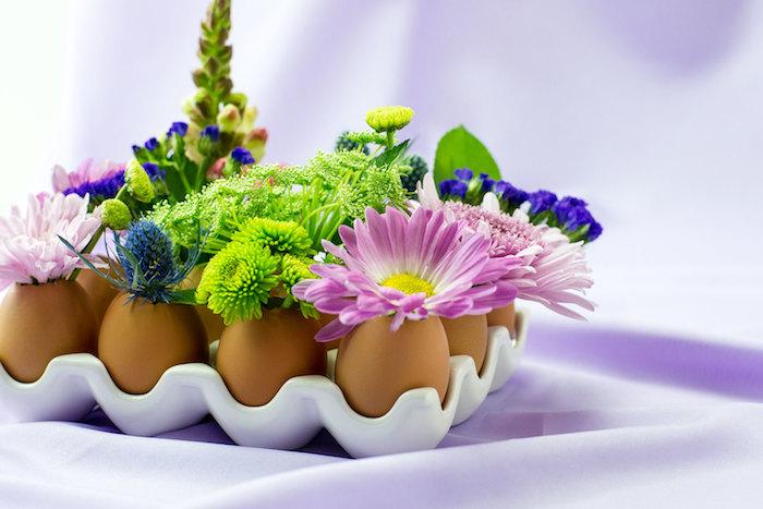modele de deco de paques avec coquille d oeuf vidée et des brins de fleurs à l intérieur, centre de table Pâques