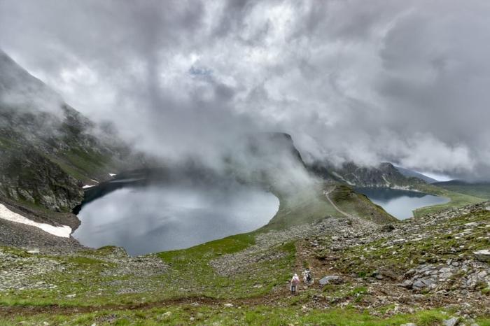 lac brumeux dans la montagne, herbe verte, roches grises, jolie paysage, vue d'en haut, ciel gris perle, touristes enthousiasmés qui grimpent vers le sommet