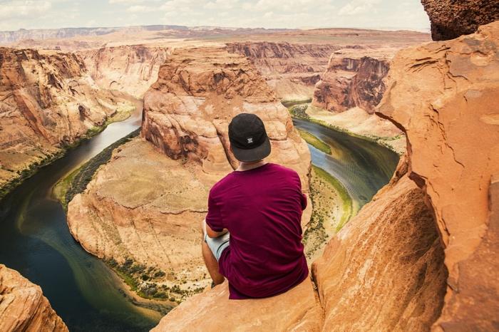 paysage paradisiaque, homme au T-shirt en bordeaux assis au bord d'une roche au-dessus d'un canyon, eaux aux nuances vertes et bleues