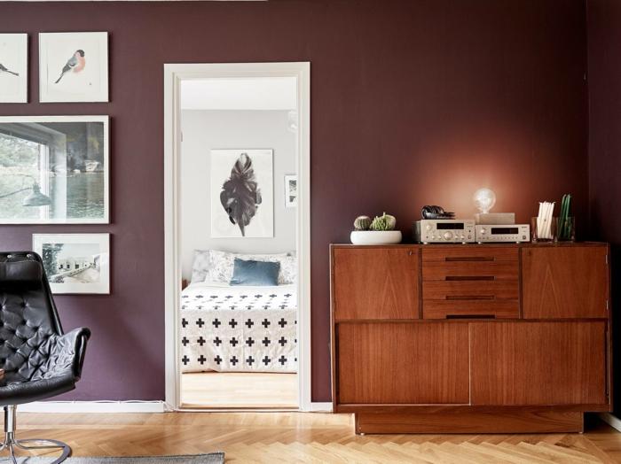 buffet vintage en bois, chaise en cuir noir, sol en parquet chevron, mur couleur bordeau