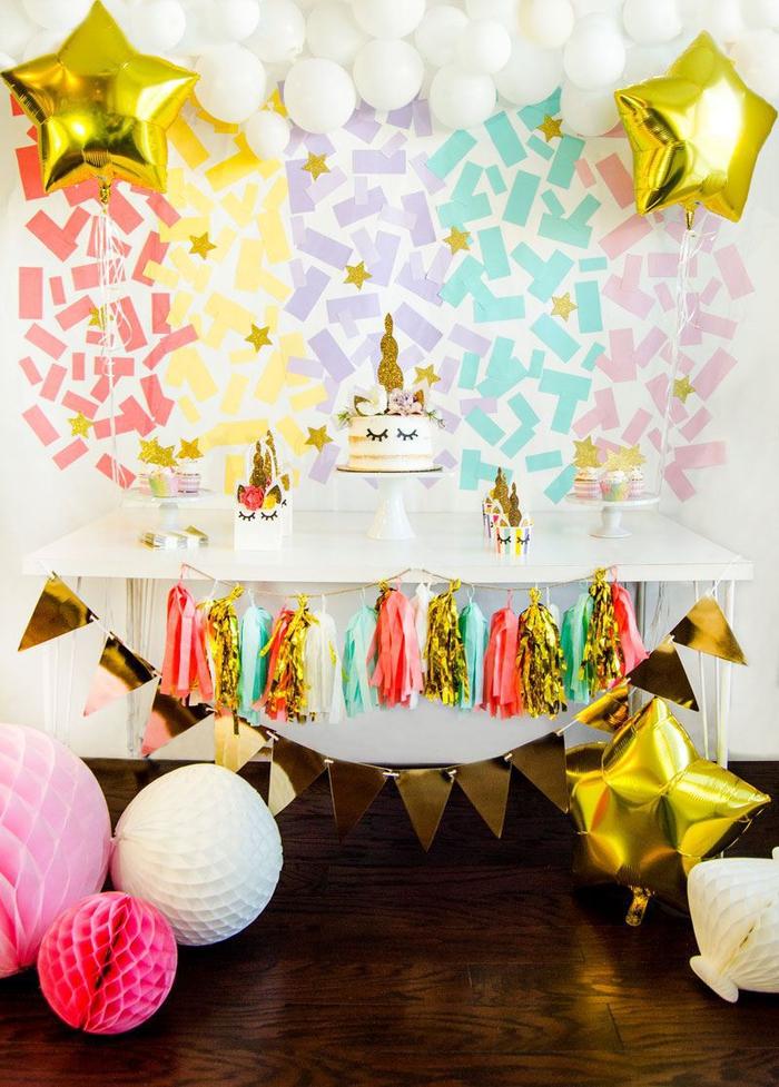 un buffet de desserts en tons pastel et doré avec une toile de fond confettis et une jupe de table en guirlande de tassels