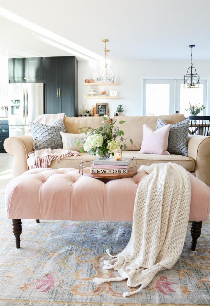 pièce aux murs blancs aménagée avec armoire noire mate aux poignées dorées, canapé beige et banc rose poudré