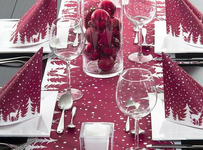nappe de table couleur bordeau, serviettes pliées, décoration avec des boules de Noel
