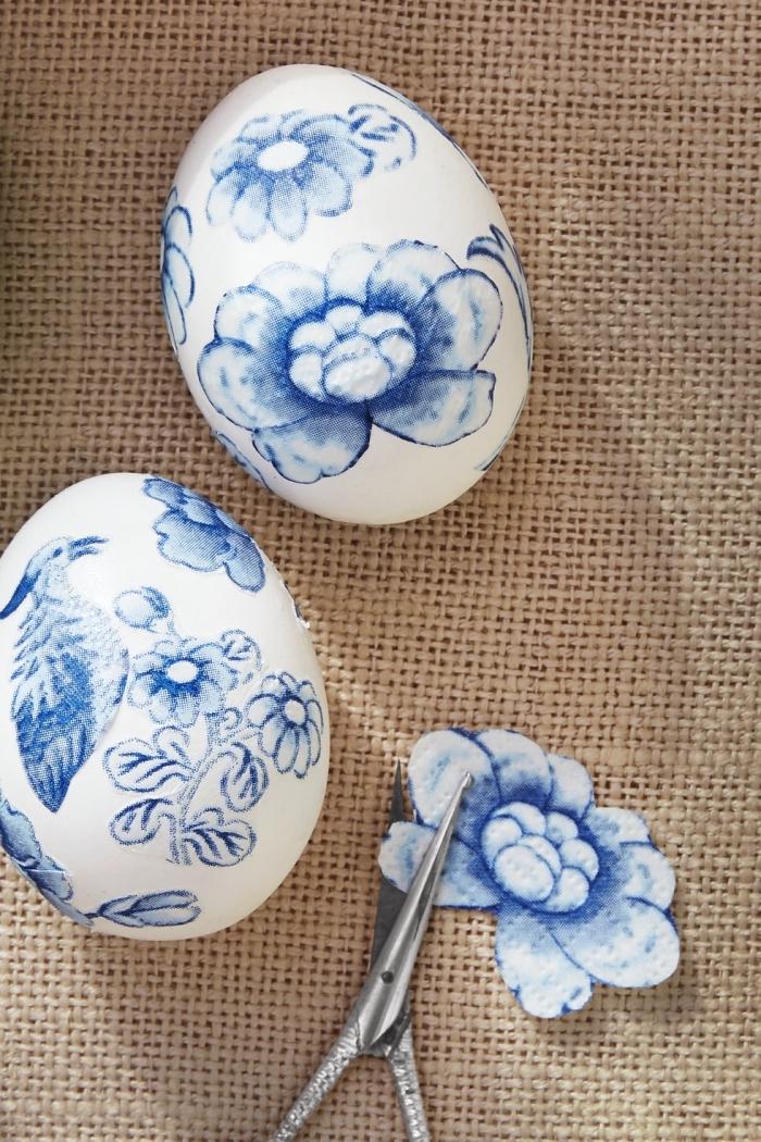 idée découpage de serviette à design floral sur une coquille blanche, modèle d'oeuf de paques en blanc et bleu