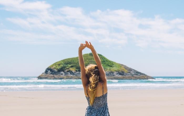 jeune fille aux cheveux ombrés sur la plage habillée en robe bleu foncé et blanc avec brettelle à design géométrique