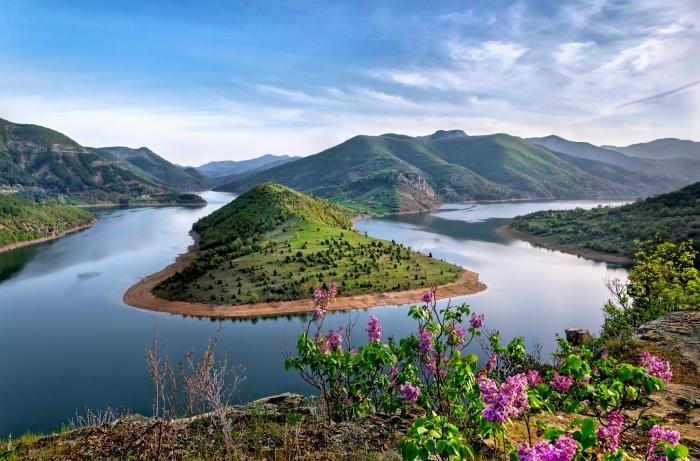 image fond d écran d'en haut avec vue vers les montagnes et eau bleue, ciel bleu aux nuages blanches et rayons de soleil