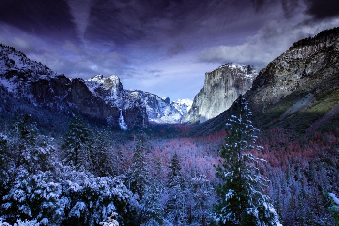 photo de forêt et collines de montagnes enneigées sous un ciel violet aux nuages grises pour un fond d'écran beau