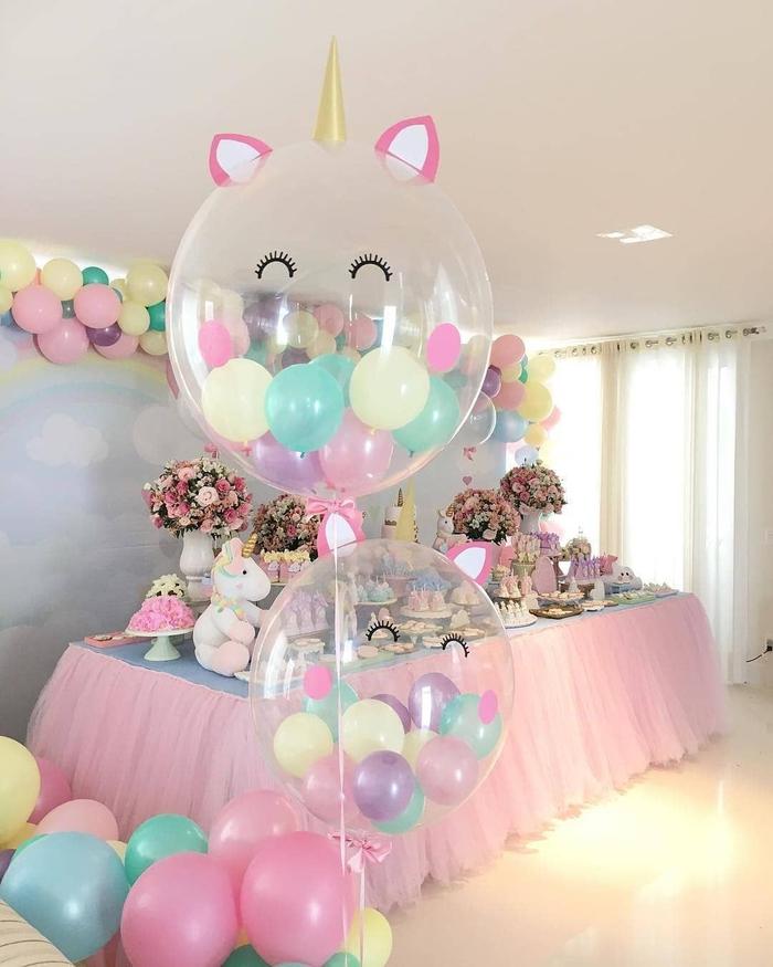 déco d'anniversaire à thème licorne avec un arc en ballons aux tons pastel et une toile de fond ciel