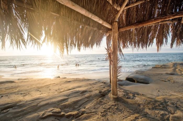 fond d écran magnifiqu au bord de la mer, photo de la plage au sable doré avec une pergola à paille et rayons du soleil
