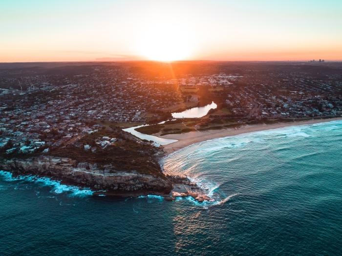 lever du soleil au-dessus d'un village pour un fond d écran jolie vue, vagues qui brisent dans les rochers pour un wallpaper ordinateur