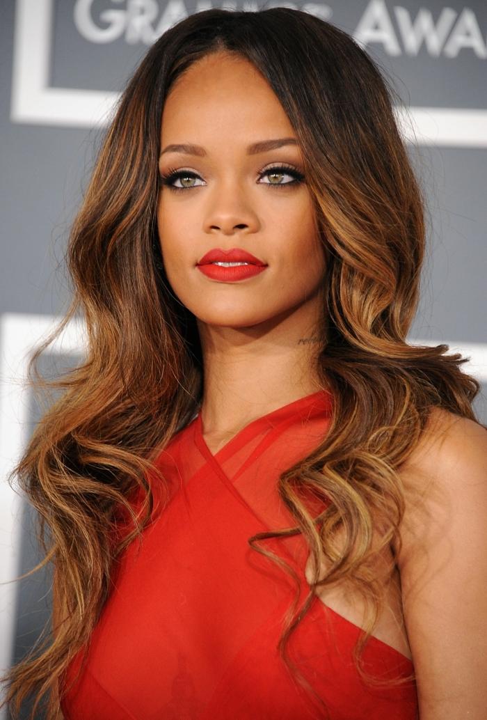coiffure bouclée de Rihanna, yeux verts, meches blondes sur cheveux chatains foncés