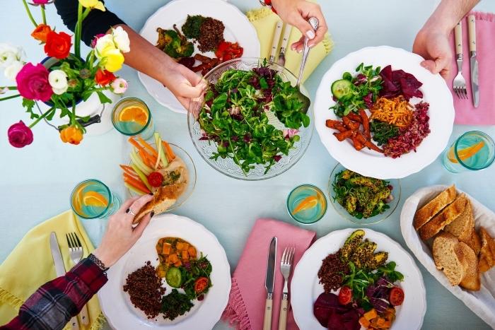 idée repas convivial entre amis, déco de table avec nappe bleu pastel et serviette rose avec franges, salade en épinards et chou rouge