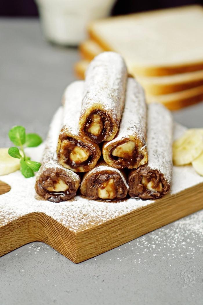 recette délicieuse de pain perdu roulé au nutella et à la banane saupoudré de sucre glace à partager entre amis