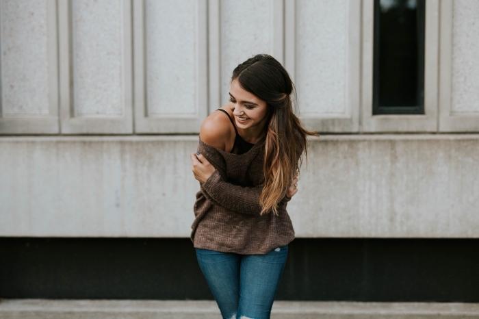 ombré hair brune, tenue comfy en jeans déchirés et pull marron avec manches tombantes, coiffure cheveux mi attachés