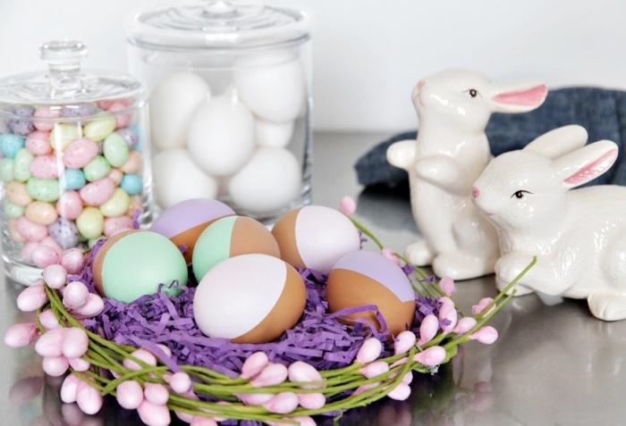 exemple de deco paques avec panier décoré en papier crêpe violet et branches artificielles, bocaux en verre remplis de bonbons oeufs colorés