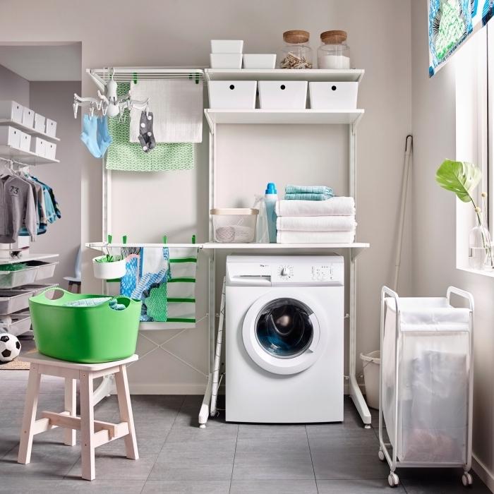 exemple d'étagère machine à laver blanche avec boîtes et étendoir mural, panier vert sur tabouret de bois clair