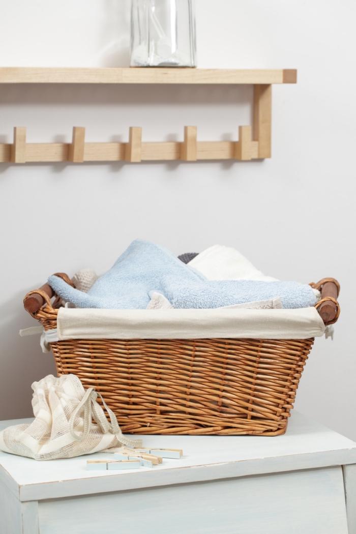 exemple de meuble buanderie fonctionnel avec étagère et patère à crochets de bois clair, armoire blanche de style shabby chic avec panier pour linge