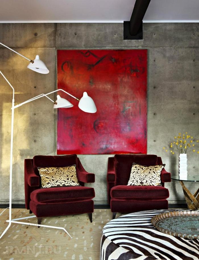 deux fauteuils couleur marsala, tableau peinture rouge, mur en béton, lampe de sol blanche