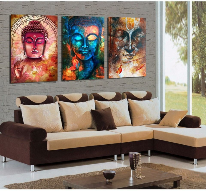 deco ethnique avec trois panneaux représentant des visages de Bouddha colorés, canapé angulaire en marron et ivoire, carrelage blanc