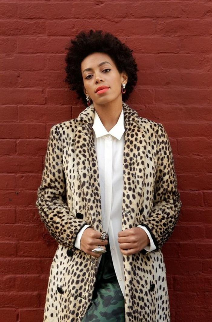 femme en veste longue aux imprimés de léopard avec des boutons noirs, jupe verte, chemise semi-transparente blanche, accessoirisée avec des grandes bagues, tenue casual, bien habillée